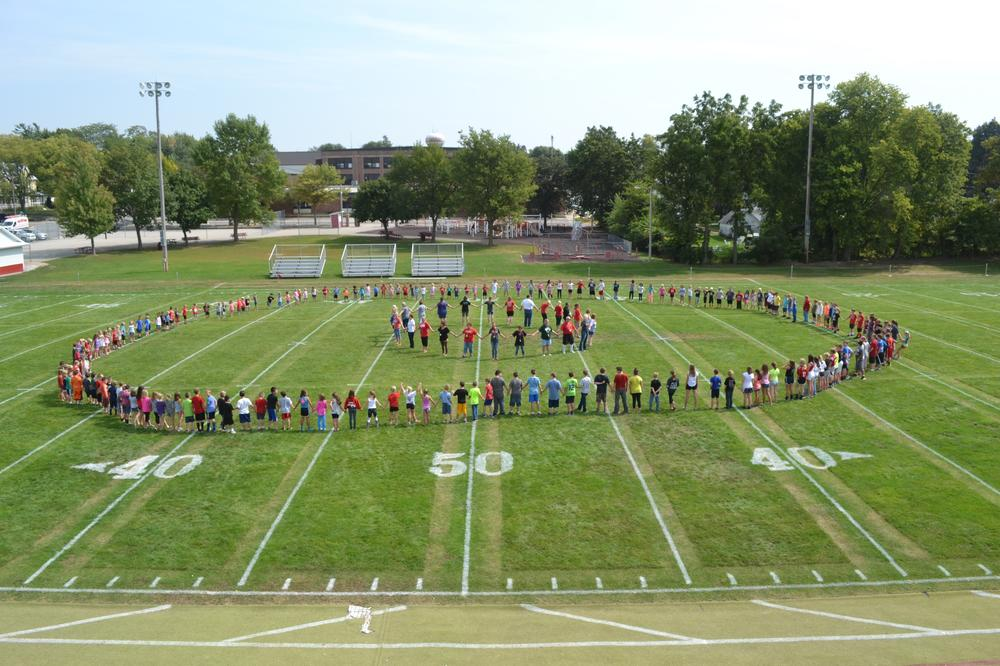 Picture of elementary students and teachers in a circle on the football field
